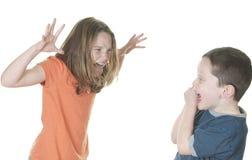 Young girl teasing boy stock image