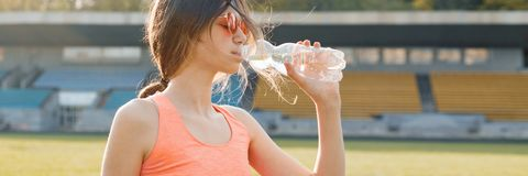 Young girl teenager drinking water from bottle after running at stadium, panoramic banner on sunny spring evening stock photography