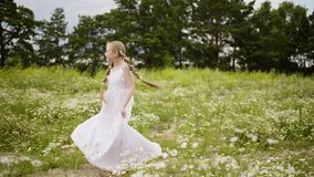 Young girl teenager with hair braid jumping on green meadow at summer. Romantic teenager girl in white dress rotating on stock video footage