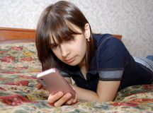 The young girl the teenager lies a bed with the cell phone. She communicates by the mobile phone by means of messengers and SMS. The young girl the teenager lies royalty free stock photo