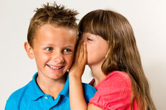 Young girl telling secret to young boy Royalty Free Stock Images