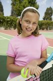 Young girl with tennis racket and ball by net at tennis court portrait Royalty Free Stock Photos