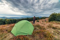 Young girl and tent in the mountains Royalty Free Stock Photo