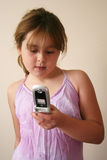 Young Girl Texting. Young girl pretending to send a text message on her toy cell phone stock image