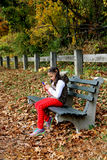 Young girl texting in the park. Royalty Free Stock Photography