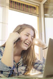Young girl texting on the phone. Young teen laughing while talking on the phone Royalty Free Stock Photography
