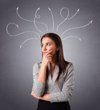 Young girl thinking with arrows overhead Royalty Free Stock Image