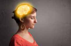 Young girl thinking with glowing brain illustration Stock Photo