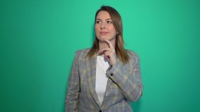 Young girl thinking and having an idea pointing hand up isolated over green background. Chromakey stock video