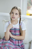 Young girl thinking while sitting on sofa Stock Photo