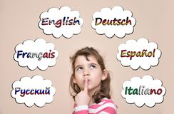 Young girl thinking which languages to learn. Thoughtful young girl thinking which languages to learn. Six different languages in the thought bubbles royalty free stock photography