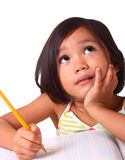 Young girl thinking and writing. Young asian girl thinking and writing Royalty Free Stock Images