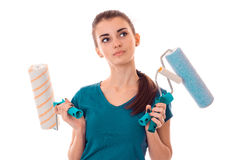 Young girl with thoughtful person holds rollers for painting walls and looks toward close up isolated on white Royalty Free Stock Images