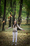 Young girl throwing autumn leaves in air Stock Photos