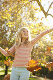 Young Girl Throwing Autumn Leaves In The Air Stock Image