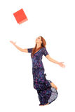 Young girl throwing a box. Young girl throwing a red box in the air Royalty Free Stock Photography