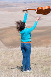 Young girl throwing guitar in the air Royalty Free Stock Photography