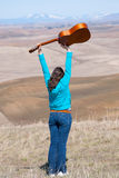 Young girl throwing guitar in the air Royalty Free Stock Images