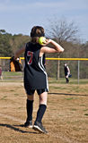 Young Girl Throwing Softball. A preteen girl throwing a softball to a teammate during a game Stock Photo
