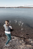 Young Girl Throwing Stones Into Water Royalty Free Stock Images