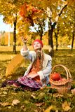 Young girl throws a bouquet of autumn leaves stock photos