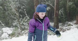 Young girl throws a snowball then claps with delight. Before reaching down to make another snowball stock video