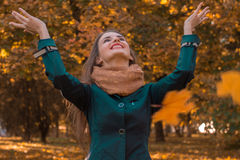 Young girl throws up the leaves in the Park and smiles Royalty Free Stock Photography