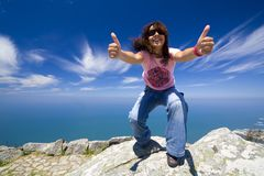 Young girl with thumbs up. In a beautifull landscape with blue water Stock Photo
