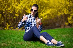 Young girl with thumbs up relax in park on fresh green grass near tree in yellow blossom. Spring time Stock Images