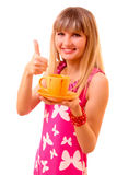Young girl thumbs up with tea cup isolated Stock Photography