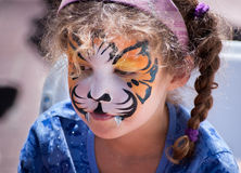 Young Girl with Tiger Face Painting. Stock Photo