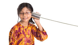 Young Girl With Tin Can Telephone IV. An Asian young girl with tin can telephone over white background Stock Image