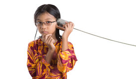 Young Girl With Tin Can Telephone VI. An Asian young girl with tin can telephone over white background Royalty Free Stock Image