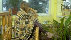 Young girl tired fit sleep and is wrapped in a blanket on a Wicker Chair at home stock video footage