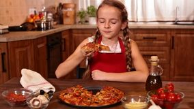 Young girl about to taste some home made pizza. Smiling with anticipation stock footage