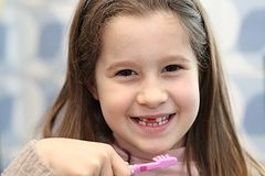 Young girl without a tooth while brushing teeth Stock Photo