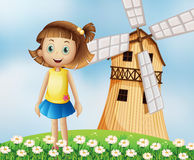A young girl at the top of the hill with a windmill Royalty Free Stock Photo
