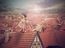 Young girl on top of the roof. Photomanipulation. Royalty Free Stock Image