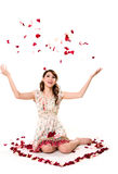 Young girl tossing rose petal. A very happy and joyfull girl tossing rose petals in the air Royalty Free Stock Photo