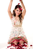 Young girl tossing rose petal. A very happy and joyfull girl tossing rose petals in the air Royalty Free Stock Photos