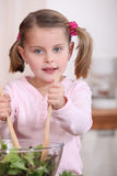 Young girl tossing a salad Royalty Free Stock Image