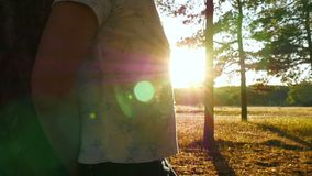 A young girl touching the tree with her back is standing in the forest at sunset. Silhouette of a girl in the woods. The slow movement of the camera up stock footage