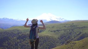 Young tourist girl with backpack gesturing success on the mountain, winner concept stock video footage