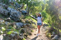 Young girl tourist in a hat on a walk on a mountain forest road, in the ruins of the ancient city Termessos in the bright rays of royalty free stock photos
