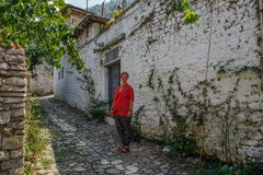 Young girl tourist in a pink blouse is standing on a cobbled road in the ancient Albanian city of Berat royalty free stock photography