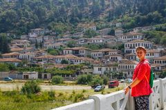 Young girl tourist in a pink blouse stands on a bridge over the river Lumi i Osumit in the city of Berat royalty free stock photo