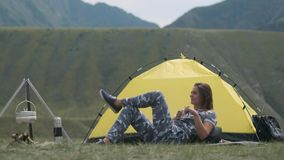 Girl tourist resting lying in front of a tent with a mug of tea on a background of mountains stock footage