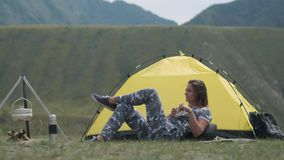Girl tourist resting lying in front of the tent with a mug of tea in her hands. Young girl tourist resting lying in front of a tent with a mug of tea in her stock footage