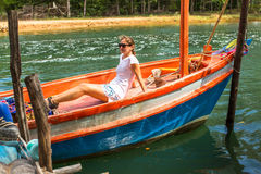 Young girl tourist sitting in a Thai fishing boat. Nature. Royalty Free Stock Photo