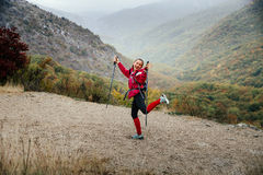 Young girl tourist with walking sticks fooling around on a mountain trail in rain Stock Photo